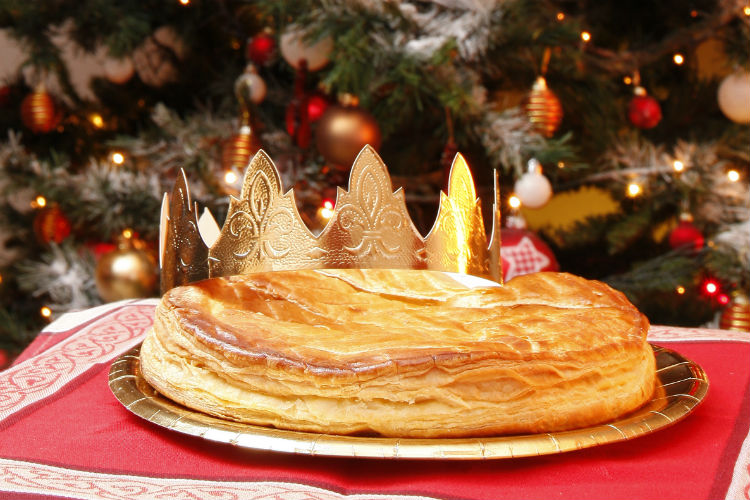 A Galette des Rois cake with a paper crown, sitting on a table in front of a Christmas Tree
