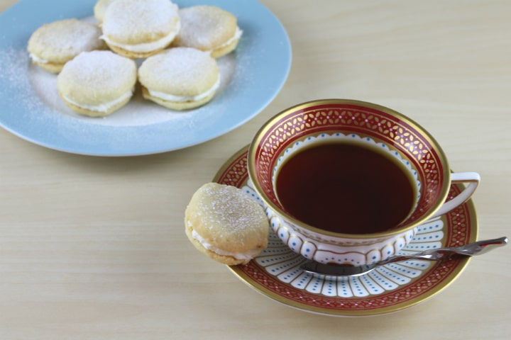 A plate of Polish Lemon Cookies with a cup of black tea
