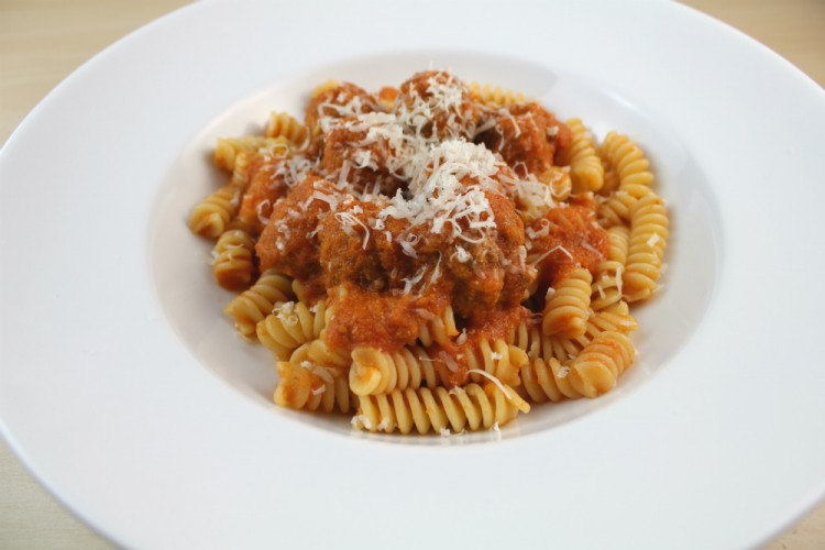 A plate of home made meatballs in tomato sauce, served with fusilli pasta