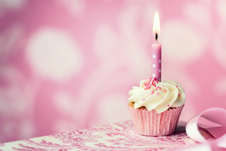 A cupcake with a lit birthday candle stuck in the frosting