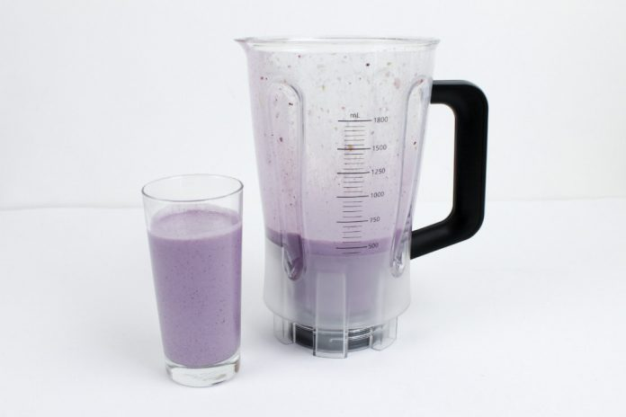 A glass of Berry Delicious smoothie next to a blender jug.