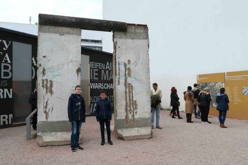 Ollie and Lyle standing in front of a section of the Berlin Wall.