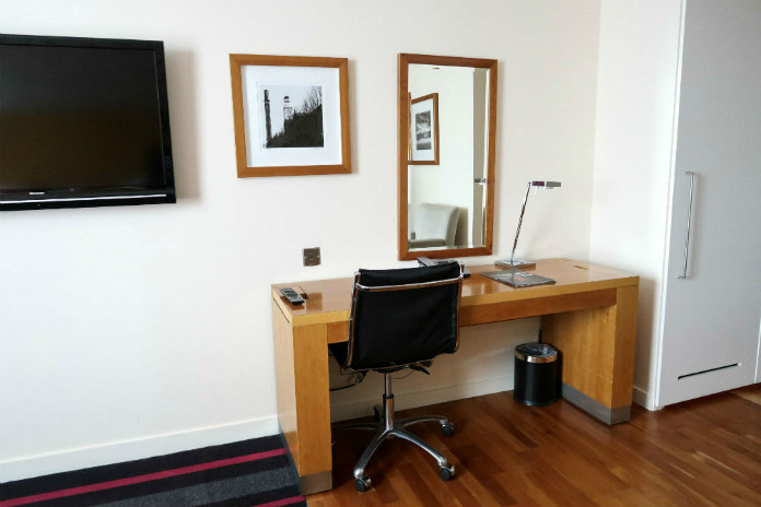 A useful desk area with plenty of charging points, in an Executive room at the Apex City Quay Hotel & Spa in Dundee