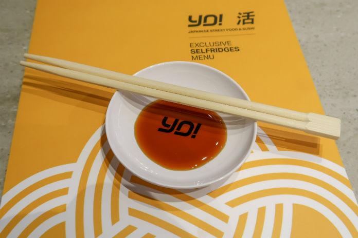 A bowl of soy sauce, chopsticks and the Yo! Sushi menu from Selfridges Birmingham