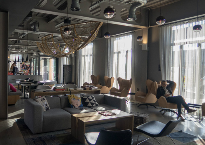 A large lounge area with plenty of comfy armchairs at the Moxy London Excel hotel