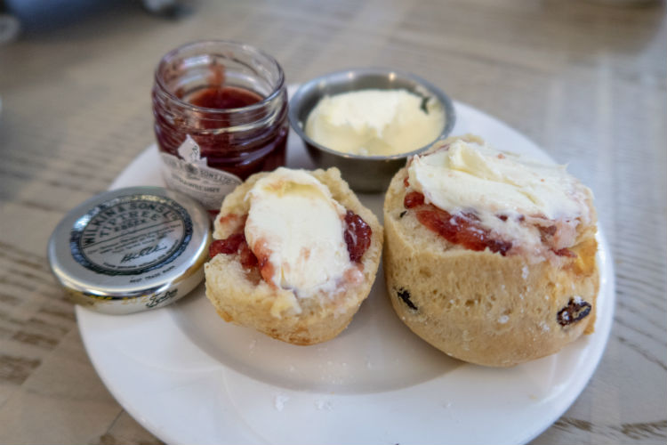 A plate containing scones spread with jam and cream for afternoon tea at the Belfry Spa, Warwickshire, UK