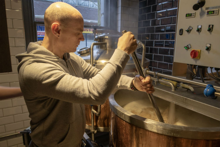 Mixing grain and water in the mash tun, at the Brewhouse & Kitchen, Lichfield, UK