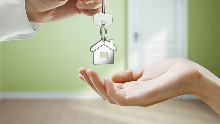 A man hands over a house key to a woman in a new home.