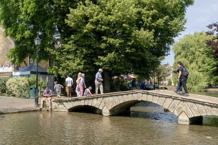 A bridge over the river flowing through the pretty Cotswolds village of Bourton on the Water, one of the destinations on my National Holidays Mystery Weekend