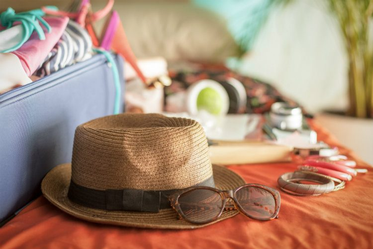 A suitcase packed full of holiday clothes and accessories, with a straw hat in the foreground