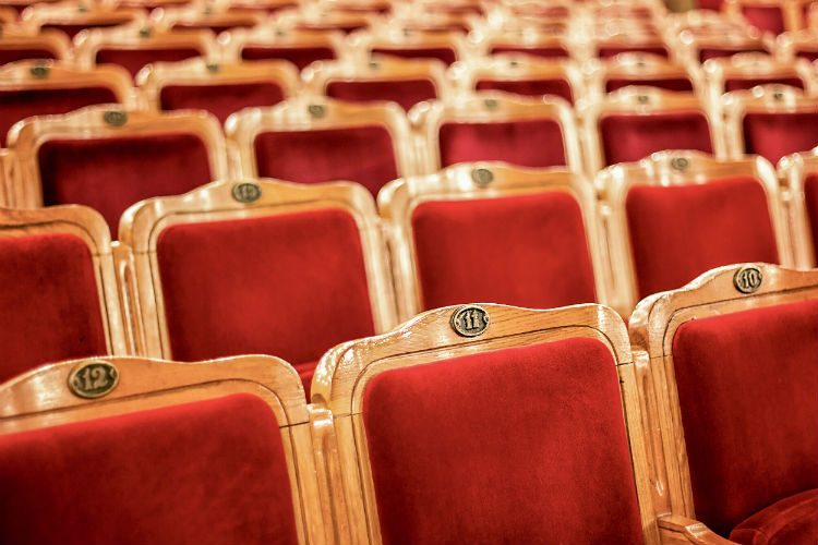 Rows of gold coloured theatre seats covered in red velvet