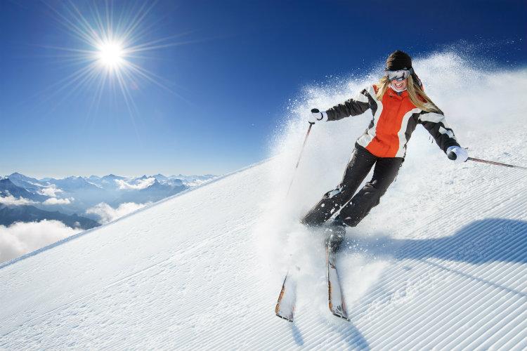 A woman skiing down a mountain against a blue sky