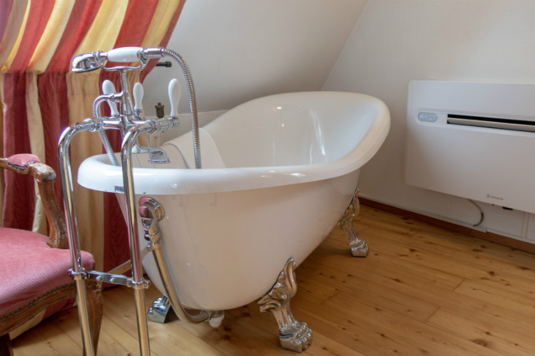 A roll top bath and modern air conditioning unit are some of the facilities in a junior suite at Hotel Drei Raben in Nuremberg, Germany