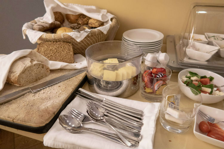 A selection of breads, cheeses and salads on the breakfast table at Hotel Drei Raben