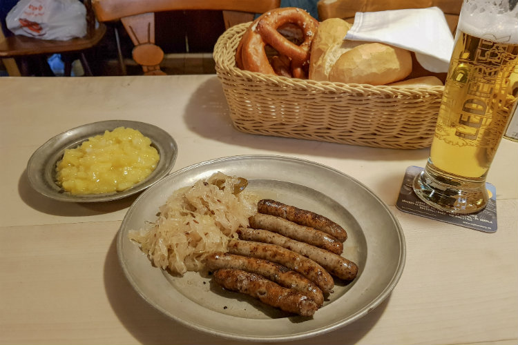 6 Nuremberg sausages served with sauerkraut, a side order of potato salad, a bread basket and a large glass of lager