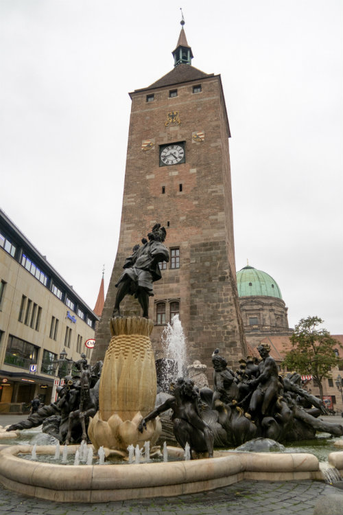 The Marriage Carousel statue in Nuremberg, Germany, with the White Tower and dome of St Elizabeth's church behind it