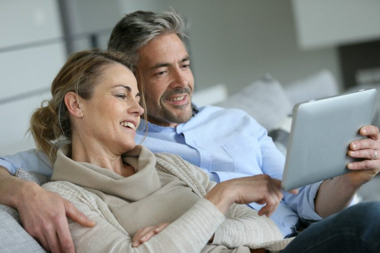 A middle aged man and woman relax on a sofa with a tablet