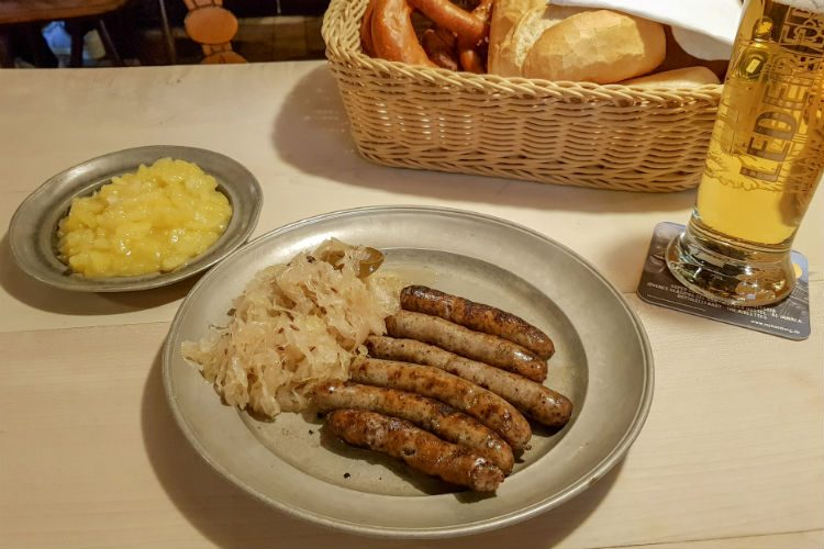 A traditional pewter plate carrying six Nuremberg sausages and a serving of sauerkraut