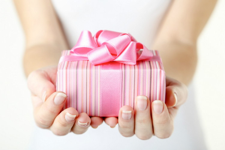 A pink wrapped gift with a pink ribbon and bow, held by a woman wearing a white dress