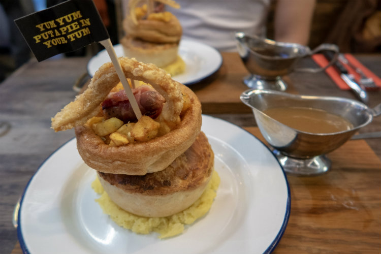 The Pieminister Christmas Cracker pie, filled with turkey and ham in a creamy sauce, with a jug of gravy alongside