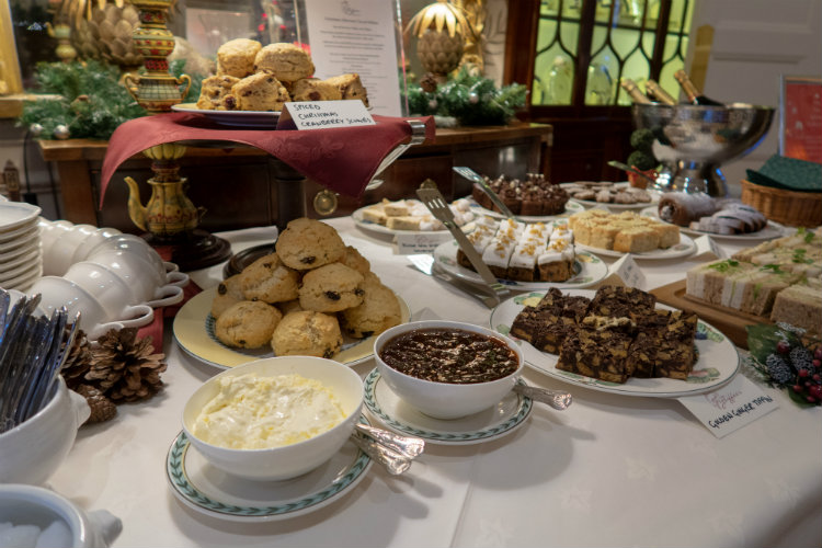 Afternoon tea at Gliffaes Country House Hotel. Plates of sandwiches, scones and cakes are arranged on a white tablecloth, and there are large white china bowls filled with clotted cream and jam