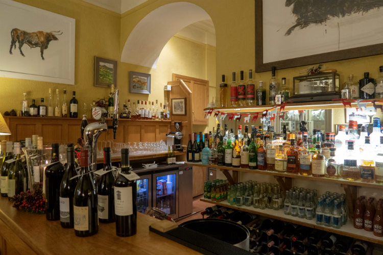 The well stocked bar at Gliffaes Country House Hotel. Bottles of wine are arranged on the bar, and there are shelves covered with bottles of spirits and mixers along the back wall