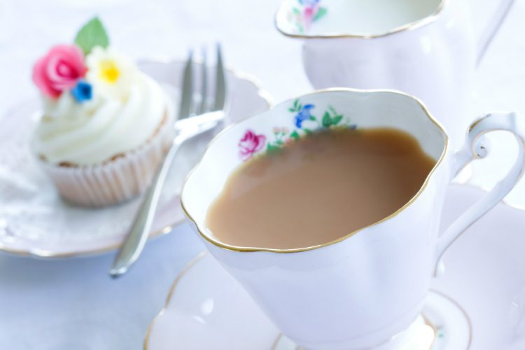 A cup of tea in a bone china cup, with a cupcake visible behind