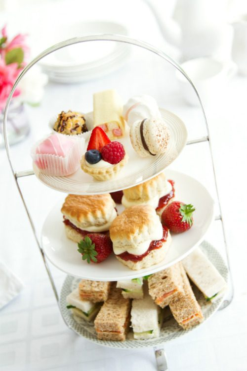 A traditional afternoon tea stand, laden with finger sandwiches, scones and little cakes