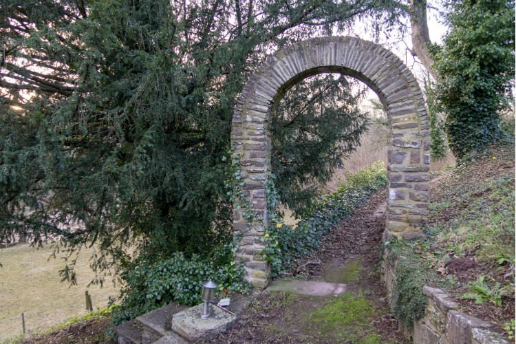 A stone archway over a pathway into the gardens at Peterstone Court, near Brecon in South Wales
