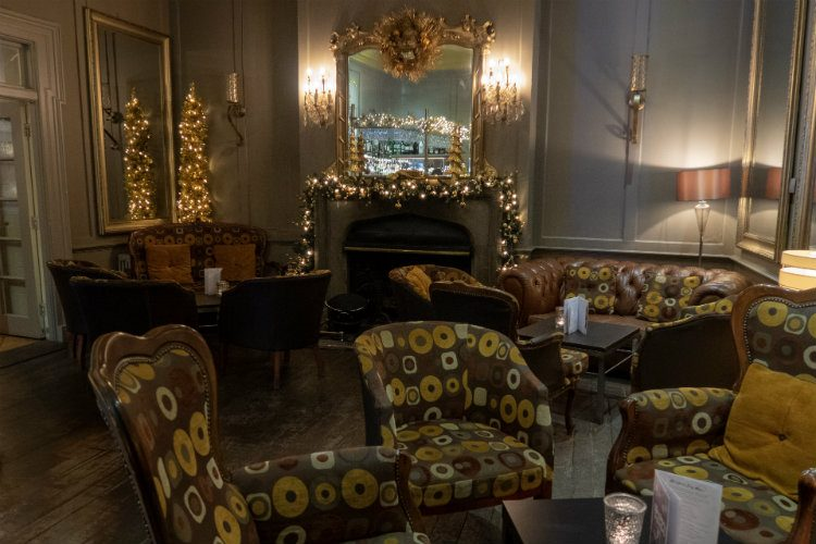 The bar at Peterstone Court Hotel & Spa, near Brecon in South Wales. There are tables with chairs and sofas dotted around the room, and a large mirror hangs above the fireplace. Christmas lights and a garland are draped across the mantelpiece