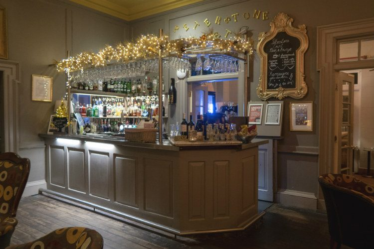 The bar at Peterstone Court Hotel & Spa, near Brecon in South Wales. The bar has glasses hanging above the bar, and shelves of bottles at the back of the room. An illuminated Christmas garland runs along the metal railing above the bar