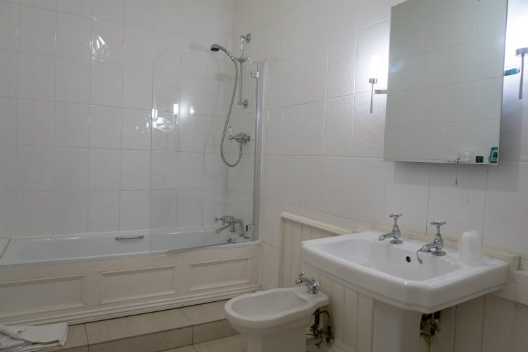 A large ensuite bathroom at Peterstone Court hotel, Brecon, South Wales. The furniture and walls are white and there are cream stone tiles on the floor. There is a shower over the bath, and a large mirror hangs over the sink
