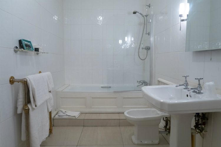 A large ensuite bathroom at Peterstone Court hotel, Brecon, South Wales. The furniture and walls are white and there are cream stone tiles on the floor. Fluffy white towels hang on a heated towel rail.