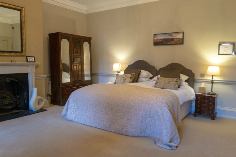 An elegant bedroom at Peterstone Court Hotel near Brecon in South Wales. The picture shows a large double bed, an antique wardrobe in the corner of the room, and a large mirror hanging over a white fireplace.