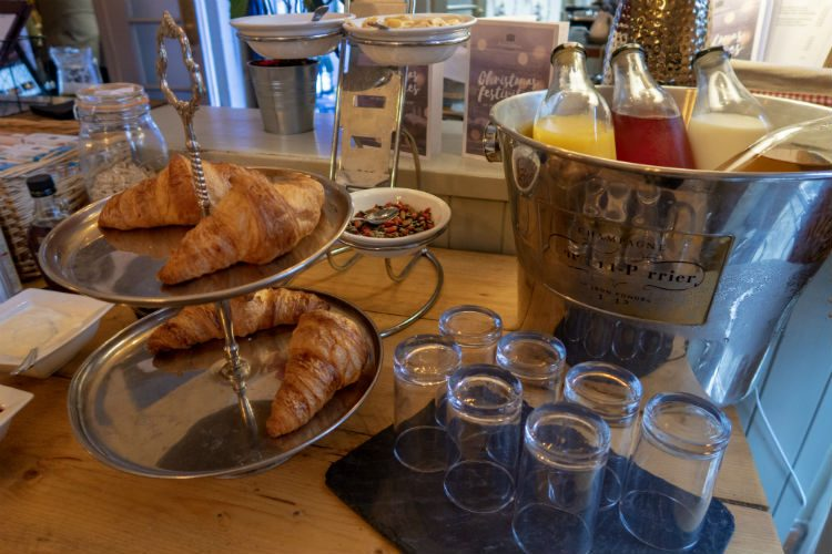 The continental buffet at Peterstone Court Hotel. Bottles of juices and milk lie in a large champagne chiller, and there are croissants on a silver cake stand