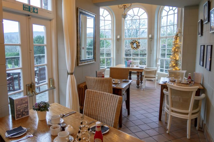 The bright and cheery conservatory at Peterstone Court, decorated for Christmas with garlands and wreaths