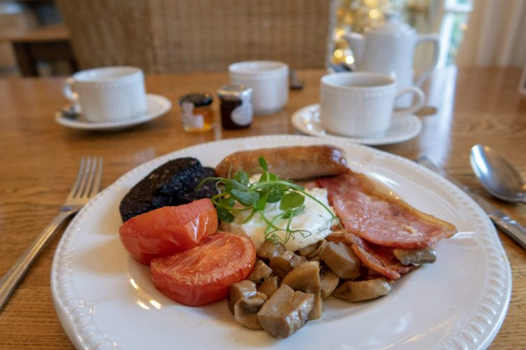 A full Welsh breakfast at Peterstone Court hotel. A white plate carrying bacon, sausage, black pudding, mushrooms, tomatoes and fried egg. A pot of coffee, coffee cup and small jars of jam are in the background