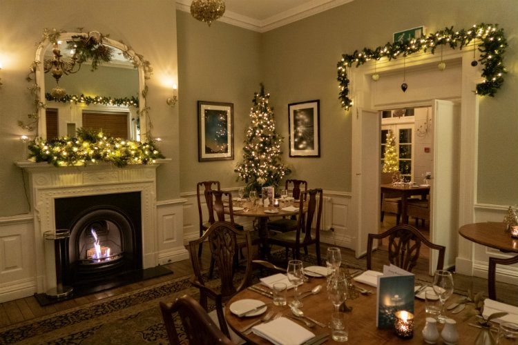 The dining room at Peterstone Court, with Christmas decorations across the door frames and Mantlepiece