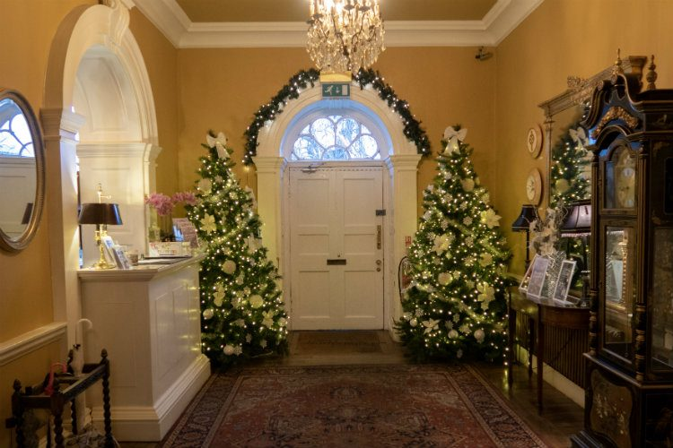 The entrance hall of Peterstone Court near Brecon in South Wales. There are two large Christmas trees either side of the white Georgian style front door, and a christmas garland runs over the top of the doorway