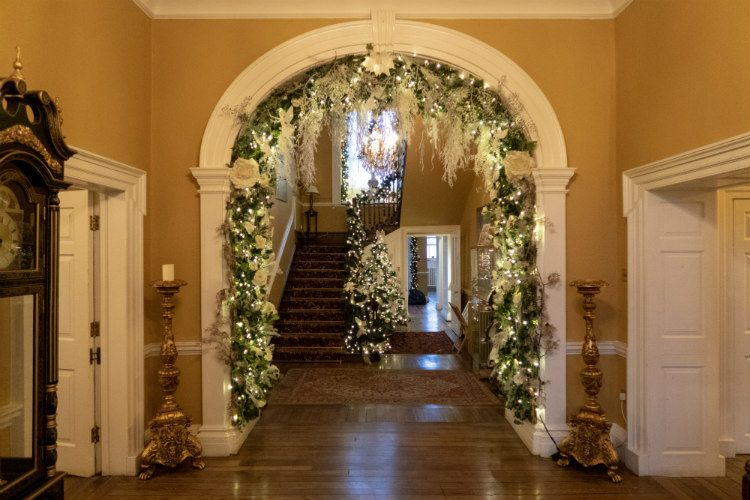The entrance hall of Peterstone Court near Brecon in South Wales. There are Christmas garlands running up the bannister of the staircase, and around the large archway in the centre of the entrance hall