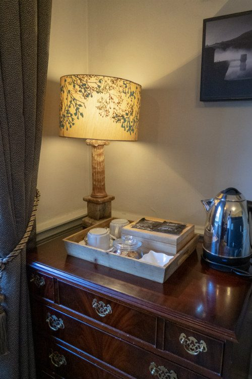 The hospitality tray in a bedroom at Peterstone Court, near Brecon, South Wales. The tray sits on an antique chest of drawers and there is a vintage style table lamp nearby.