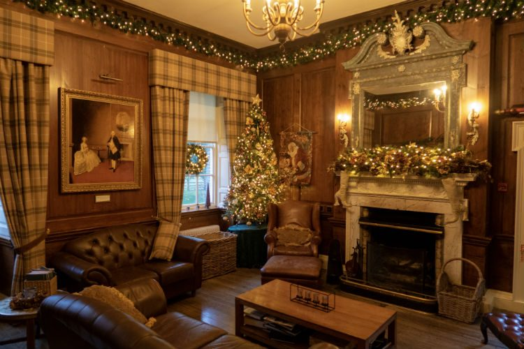 The library at Peterstone Court Hotel and Spa, Brecon, South Wales. The walls are covered in wood panelling, and checked curtains hang at the windows. There is a large Christmas tree in the corner of the room, and garlands run around the picture rail at the top of the walls. A large mirror hangs above the elaborate fireplace, and there is a christmas garland on the mantelpiece