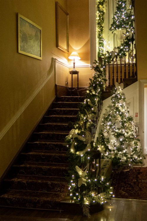 The staircase up to the bedrooms at Peterstone Court Hotel in South Wales. A Christmas tree stands in the corner of the hallway, and there is a garland draped along the bannister leading upstairs