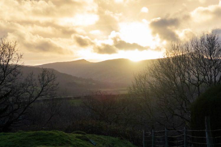 Sun sets over Pen y Fan, behind Peterstone Court near Brecon in South Wales