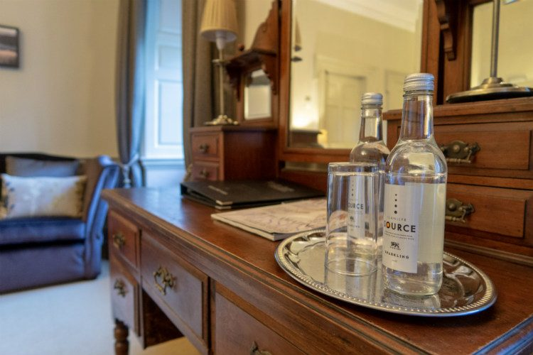 Two bottles of water and two glasses on a silver tray, sitting on the antique dressing table in a bedroom at Peterstone Court, Brecon, Wales