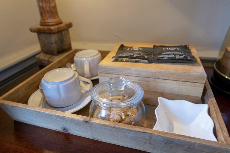 Close up on the hospitality tray in a bedroom at Peterstone Court, near Brecon, South Wales. A box contains tea and coffee, and there are two cups and saucers as well as a jar of home made cookies