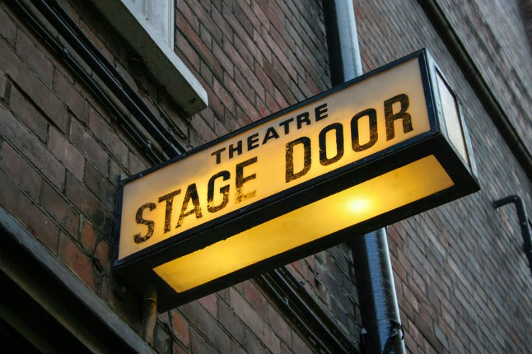 A stage door illuminated sign, with a yellow light and the words'Stage Door' in black letters