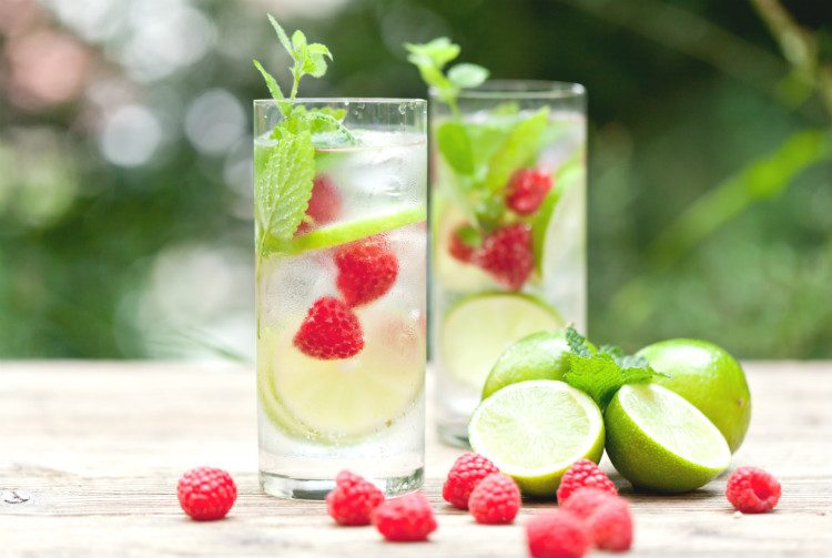 Glasses of water with lime, mint and berries