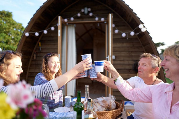 A family enjoy a celebratory drink in front of a Wigwam®Holidays glamping chalet