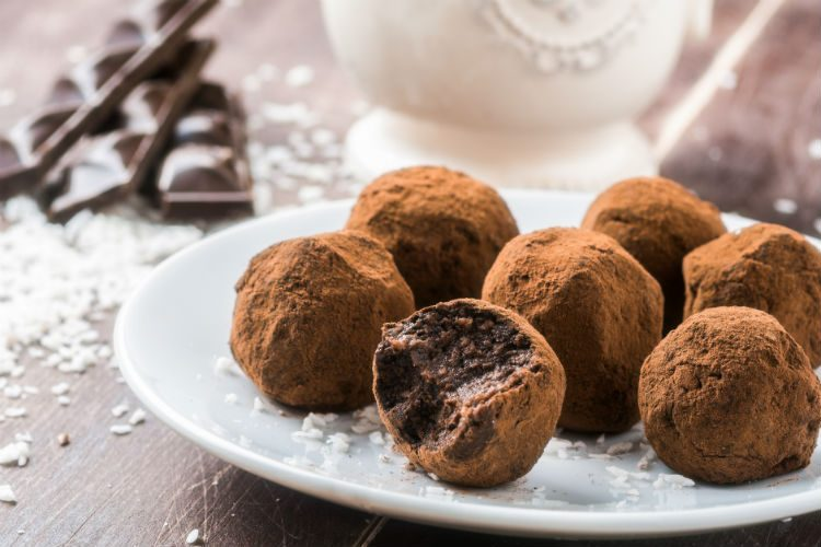Home made chocolate truffles on a white china plate, with chocolate and coconut in the background